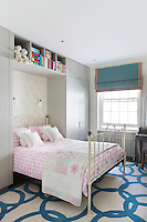 Built-in wardrobes flank the pink and white gingham bed in a child's bedroom