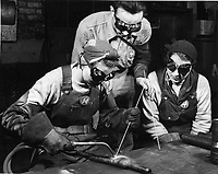 Peggy Bridgeman at the left demonstrates to Ruth Harris the correct technique while their instructor, Lee Fiscus, looks on attentively, in the Gary plant of the Tubular Alloy Steel Corporation, United States Steel Corporation subsidiary. Peggy is acclaimed by her superiors to be one of the most skilled welders they have had working with them. undated photo - probably during World War II. <br /> Date unknown