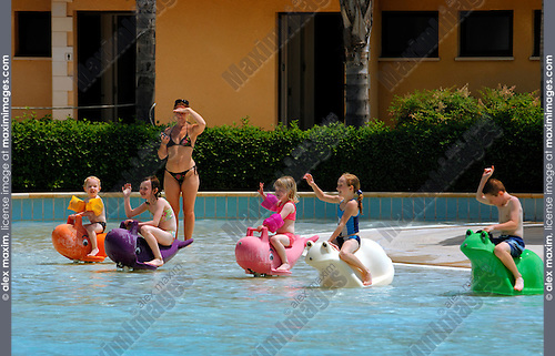 Stock photo of a Children playing in a pool and an adult woman looking after them Fasoury Watermania water park Cyprus Summer 2007 Horizontal Summer vacation activities healthacre health lifestyle recreational concept