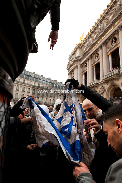 Young men try to set fire to an Israeli flag during a protest by several thousand people against Israel's military offensive in the Palestinian Gaza Strip in front the Palais Garnier opera house in Paris, France, 17 October 2009.