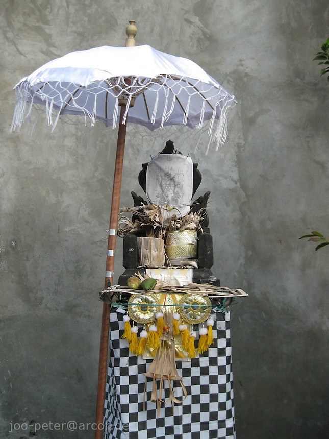 house shrine with white umbrella and offering in Lovina, Bali, archipelago Indonesia, 2009