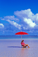 Woman reading under red umbrella in water at a beach on the windward side of Oahu.