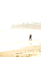 Lone surfer on the beach, Carlsbad, California.