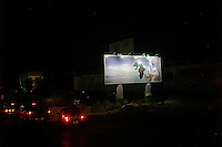 Tripoli, Libya, March 23, 2011. .In this image taken during an organized trip by the Libyan authorities, a giant Khaddafi portrait hangs on a roadside billboard.