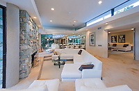 Living room with white sectional sofa, walls of glass and river rock fireplace