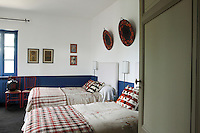 In this blue and white twin bedroom the throws are from Slovenia and the bedcovers are hand-painted designs by Fanni Chambas