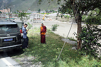 A Tibetan monk stand by the side of the road in the south-east Tibetan Plateau, in Sichuan Province, western China.