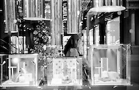 Milano, zona centro. Negozi addobbati per Natale in corso Vittorio Emanuele. Una donna in una gioielleria --- Milan, downtown. Shops decorated for Christmas in Vittorio Emanuele street. A woman in a jewelry store