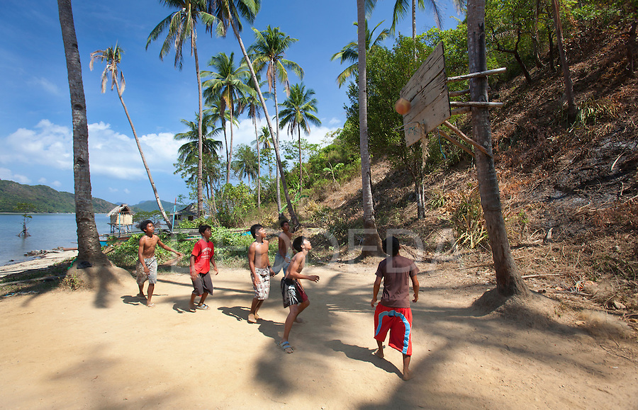 A group of teenage boys play basketball with the hoop attached to a coconut tree in the tiny fishing village of Vigan near Snake Island and El Nido, in the Bacuit Archipelago in Palawan, Philippines.