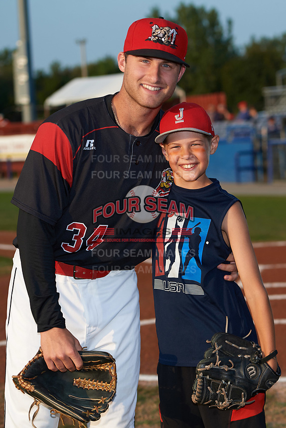 Batavia Muckdogs infielder Bubba Hollins (34) poses for a photo with one of the teams youth baseball clinic's participants who threw out the ceremonial first pitch before a game against the Mahoning Valley Scrappers on August 30, 2017 at Dwyer Stadium in Batavia, New York.  Batavia defeated Mahoning Valley 5-1.  (Mike Janes/Four Seam Images)