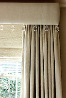 Tear-drop shaped crystals hang from the edge of this linen-covered pelmet