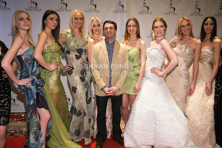 Fashion designer Edward Arsouni poses with models pose on red carpet after the Edward Arsouni fashion show, during Couture Fashion Week Fall 2011.