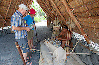 Visitors watching native Hawaiian man make Hawaiian artifacts in Pu'uhonua o Honaunau National Historical Park, Big Island.