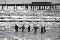 May 23, 2013: Ocean Beach, San Diego, California, USA:  At the San Diego Lifeguard Bronze Memorial Dedication Ceremony, 13 Lifeguards representing the 13 victims of the 1918 drownings made their way to the water and formed a ceremonial circle.