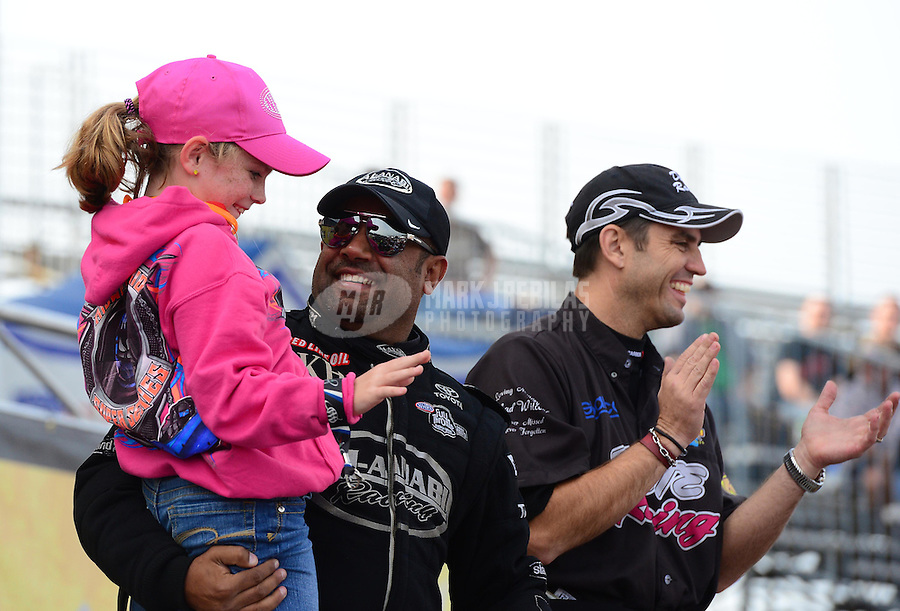Sept. 30, 2012; Madison, IL, USA: NHRA top fuel dragster driver Khalid Albalooshi (left) holds a little girl alongside Larry Dixon during the Midwest Nationals at Gateway Motorsports Park. Mandatory Credit: Mark J. Rebilas-
