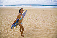 Local Asian woman with surfboard walking down Ehukai Beach to go surfing