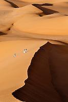 Aerial view of a group of Tuareg men walking in sand dunes of the Ubari Desert in the Libyan Sahara
