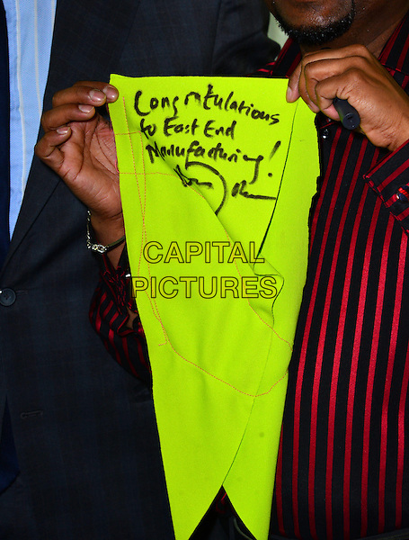 Fabric.Boris Johnson visits newly established clothes manufacturer in East London, East End Manufacturing Ltd., London, England..26th February 2013.gv general view yellow green neon fluorescent congratulations to signature.CAP/BF.©Bob Fidgeon/Capital Pictures.