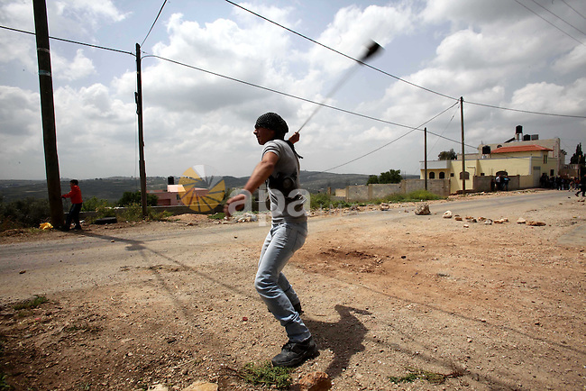 A Palestinian protester uses a sling shot to hurl stones towards Israeli security forces during clashes following a protest Palestinian Prisoner's Day and against the expropriation of Palestinian land by Israel in the West Bank village of Kafr Qaddum, near the northern city of Nablus, April 17, 2015. The current number of Palestinians held in Israeli prisons is at least 6,200 and is the biggest for at least five years, according to figures from rights groups. Photo by Nedal Eshtayah