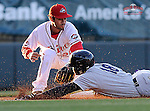 Designated hitter Abiatal Avelino (18) of the Charleston RiverDogs slides in safely with a triple as Greenville Drive third baseman Carlos Asuaje (20) applies a late tag in a game on Wednesday, April 16, 2014, at Fluor Field at the West End in Greenville, South Carolina. (Tom Priddy/Four Seam Images)