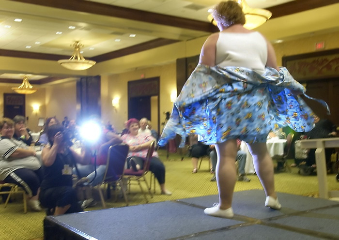A participant in The National Association to Advance Fat Acceptance (NAAFA) Lingerie Fashion Show twirls for the audience at the group's annual convention at the Newark Liberty Airport Marriot in Newark, NJ, this weekend. The group denounces dieting but supports exercise for healthy living. Thursday, August 5, 2004. ( James J. Lee / The Washington Times )