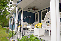 House porch with ceiling fan, blue and white motif, white wicker furniture and planter, yellow flowers in container