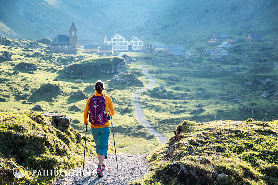 A woman hiking in the Alpstein region of eastern Switzerland. In front of her is the tiny village of Meglisalp which sits isolated within the mountains and is an old dairy farming community during the summer months.
