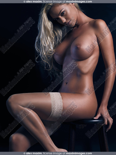 Artistic nude photo of a sexy young naked woman in stockings sitting on a stool isolated on black background