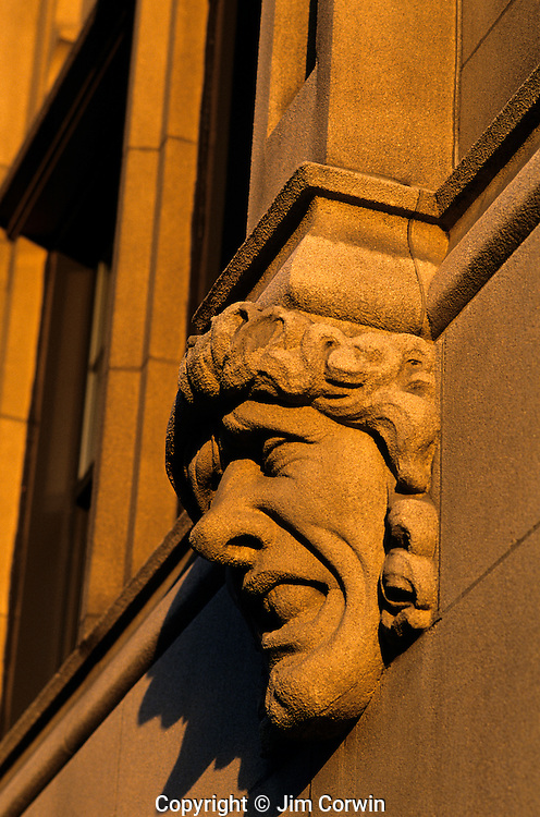 """Gargoyle on side of building at sunset grotesque expression on face along the """"Ave"""" University District Seattle Washington State USA"""