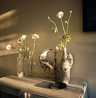 White flowers displayed in glass bottles and a stone vase are arranged on a table made from reclaimed wood.