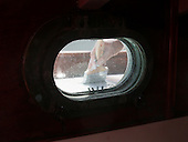Looking thru a porthole on a boat, one sees a hand and paint brush, painting the deck.