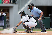 Charlotte Knights catcher Omar Narvaez (14) back-hands a pitch in the dirt as home plate umpire Ryan Additon looks on during the game against the Gwinnett Braves at BB&T BallPark on May 22, 2016 in Charlotte, North Carolina.  The Knights defeated the Braves 9-8 in 11 innings.  (Brian Westerholt/Four Seam Images)