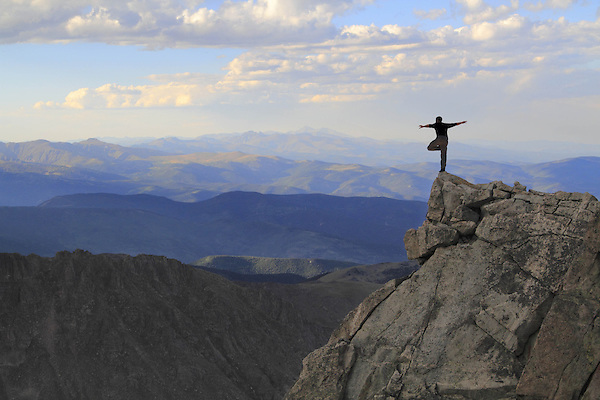 Man balancing of the edge of a cliff on Mount Evans (14250 feet) in the Rocky Mountains west of Denver, Colorado. Guided photo tours and hiking tours to Mt Evans.