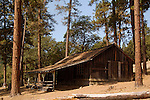 An old livery stable sits among the trees in the historic ghost town of Buncom, Oregon