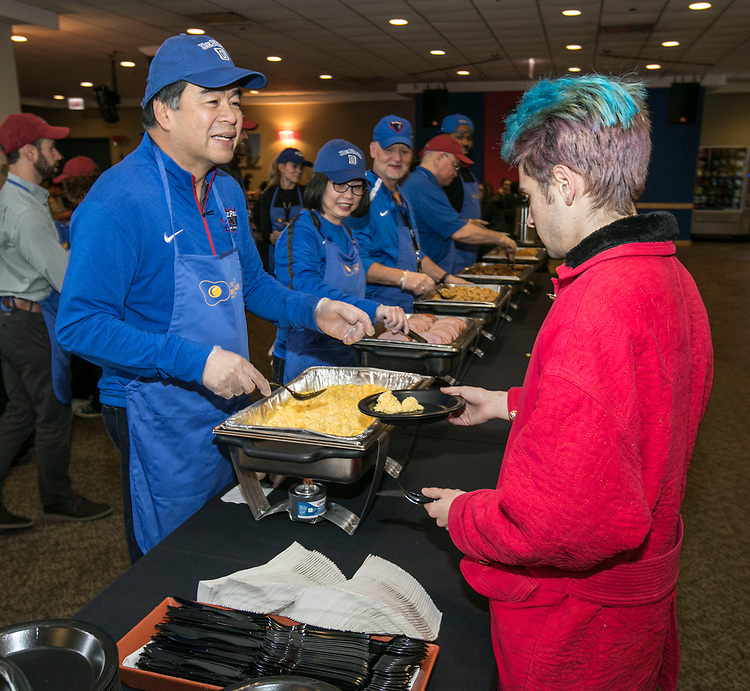 President A. Gabriel Esteban, Ph.D., and his wife, Josephine, team up with Gene Zdziarski, vice president for Student Affairs, (left to right) as they offer breakfast to study-weary students, Tuesday, Nov. 14, 2017, during the Midnight Breakfast at the Student Center on DePaul's Lincoln Park Campus. More than 1,250 students gathered in the dining hall for a Student Affair's sponsored breakfast of eggs, sausage, hash browns, ham and pancakes. The event also featured stress-relieving games and prizes for students studying for their exams before the holiday break. (DePaul University/Jamie Moncrief)