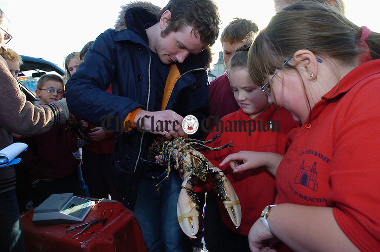 Aine Fahey and Karen O Toole of Ballyvaughan National School helping Eoin Kelly of NUIG with the tagging of live lobsters for conservation and breeding management purposes at the opening of the new pier in Ballyvaughan. Photograph by John Kelly.