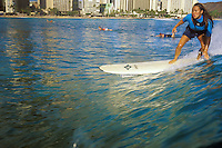 Photograph taken from sea level of local girl surfing off Waikiki with Waikiki Beach in the background.
