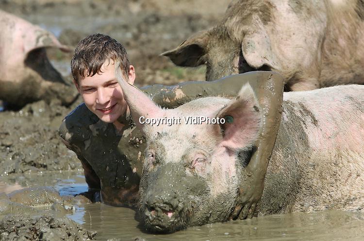 Foto: VidiPhoto<br /> <br /> HEDEL - De fokzeugen van varkenshouder Andries van den Bogert uit Hedel in de Bommelerwaard hadden dinsdag plotsklaps geheel ander vlees in de kuip. De 18-jarige Jochem van den Bogert wilde aan den lijve ondervinden wat varkens ervaren als ze een modderbad nemen. En daarom ging hij samen met een deel van 130 zeugen in bad. &quot;Aangenaam en zeker voor herhaling vatbaar&quot;, was zijn conclusie. Jochem neemt straks de biologische varkenshouderij van zijn vader over. Zijn studie aan het Helicon (afdeling veehouderij) in Den Bosch is daar ook op gericht. Van de Bogert heeft 130 biologische zeugen en 900 vleesvarkens die zelf naar buiten kunnen als ze dat willen. De modderpoel maken ze zelf steeds groter.