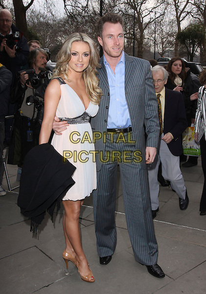 OLA JORDAN & JAMES JORDAN .The TRIC Awards 2010 (Television and Radio Industries Club) held at the Grosvenor hotel - outside arrivals London, England, UK, March 9th 2010..arrivals full length grey gray suit blue shirt couple husband wife pale peach pink dress cream embellished waistband jewelled tie dye ombre .CAP/AH.©Adam Houghton/Capital Pictures.
