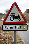 Red triangular road sign for farm traffic, UK