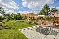 BNPS.co.uk (01202 558833)<br /> Pic: Mullucks/BNPS<br /> <br /> Garden after.<br /> <br /> A retired couple dubbed 'the accidental upsizers' have put their luxury home on the market for a whopping £750,000.<br /> <br /> Jean and Desmond Lawton bought a suburban bungalow three years ago as they looked to downsize from a large property.<br /> <br /> But they soon decided that they didn't like the dated decour of the humble home and transformed it beyond recognition.<br /> <br /> They knocked down every internal retaining wall bar one to create an open-plan space and built a single-storey extension to the rear.