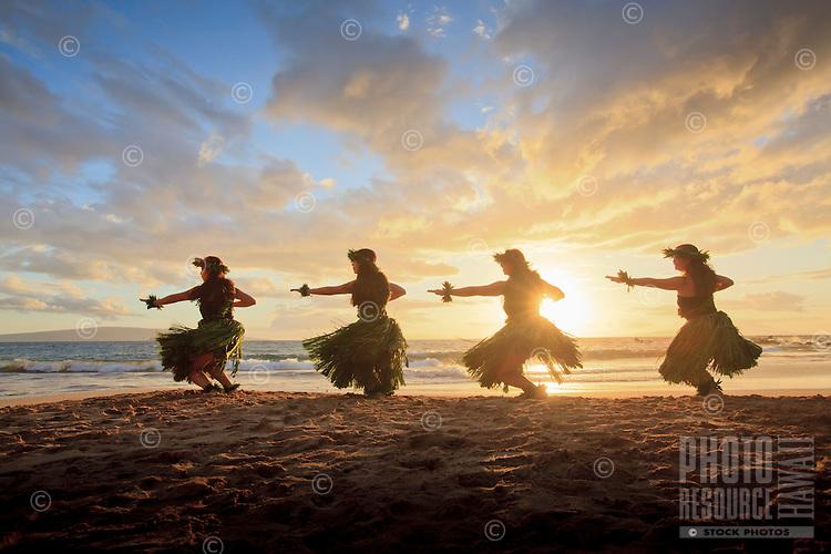 Four hula dancers at sunset at Palauea, Maui, Hawaii, backlit by the sun.