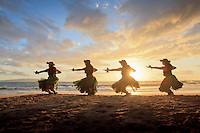 Four hula dancers at sunset at Palauea, Maui, Hawaii, backlit by the sun.