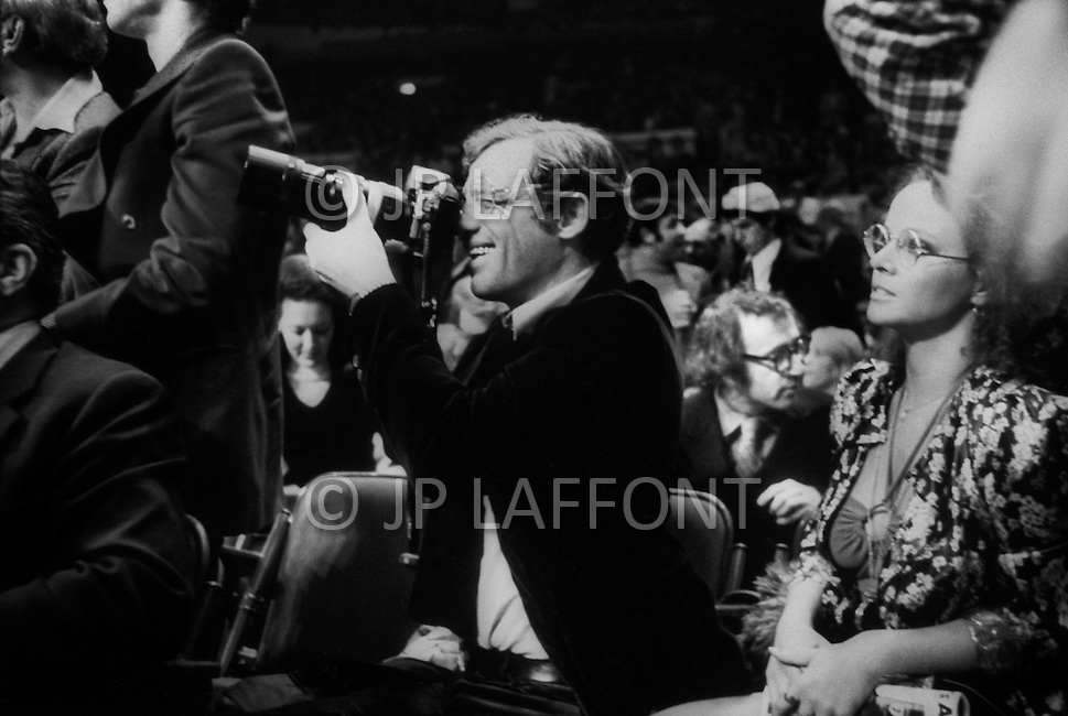"Jan 23, 1974, Madison Square Garden, NY. The revenge match between Muhammad Ali and Joe Frazier. Ali won this match. The french actor Jean-Paul Belmondo taking pictures of the match with his girlfriend Laura Antonelli. Behind them Woody Allen who just finished his movie ""Sleeper""."
