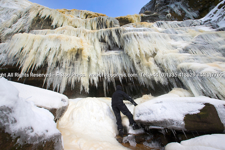 02/02/15<br /> <br /> A climber marvels at icicles forming columns of ice as the whole of a 30 metre waterfall freezes solid.  At 2,087 ft the cascade known as Kinder Downfall is the only mountain in the Derbyshire Peak District and famously blows up hill in strong winds. <br /> <br /> All Rights Reserved - F Stop Press.  www.fstoppress.com. Tel: +44 (0)1335 418629 +44(0)7765 242650