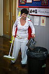 © Joel Goodman - 07973 332324 . 7th November 2013 . Godfrey Ermen C of E Primary School , School Road , Eccles , M30 7BJ , UK . Kitchen staff member dressed as Elvis , cleaning the floor after lunch . Children come to school dressed up in the fashions of the past 110 years to celebrate the school's 110th birthday . Photo credit : Joel Goodman