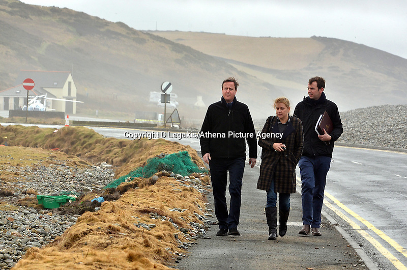 Pictured: Prime Minister David Cameron (L) walking by the storm damaged coastal road in Newgale, Pembrokeshire. Wednesday 19 February 2014<br /> Re: Prime Minister David Cameron has today visited the Pembrokeshire village of Newgale which suffered severe damage during the early January and February storms.