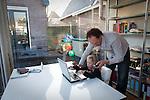 Nederland, Amsterdam, 12-12-2008  Jonge vader werkt in zijn kantoor container achter zijn huis en past tegelijkertijd op zijn vier jarige dochter.  (model released) . FOTO: Gerard Til