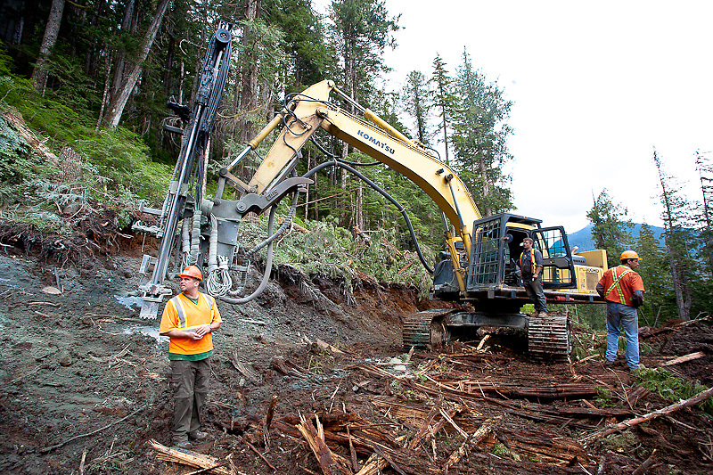 Ryan Ricard (Forestry Engineer, Interfor) and Glen Kappel (Logging Manager, Olympic Forest Products) look over new road construction at Chamiss Bay, Vancouver Island, July 2012. Bill Hankins (driller/excavator operator) takes a moment away from the dust and noise to enjoy the scenery.