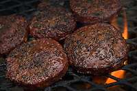 Flames from a charcoal grill lick the edge of hamburgers covered in grilling spices
